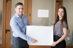Your advertisement in good hands. Group of handsome young business people holding big blank with copy space Stock Photo