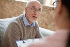 Caregiver writing graphic for surprised senior man. Your agenda. Amazed pleased senior men sitting on blurred background while gazing at caregiver and stock photography