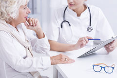 Your blood readings got better. Woman doctor explaining the medical results to the senior woman royalty free stock photography