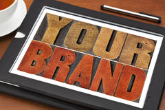 Your brand word abstract. Motivational concept in vintage letterpress wood type block on a digital tablet with a cup of tea royalty free stock image