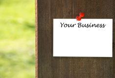 Your business inscription on white note paper with a wooden background Royalty Free Stock Images