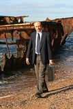 Is this your business's future. Businessman on the beach by an old wreck, dressed in business attire in front of a very old rusting shipwreck on the beach, with stock photography