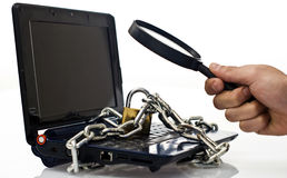 Your data is secure?. Laptop isolated on white with chains around and with magnifier looking at the locker Stock Image