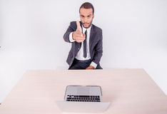 Your dealings. Smiling African businessman sitting at a desk on Stock Images
