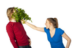 In your face. Woman hitting her husband in the face with a bunch of parsley in a food fight Royalty Free Stock Images