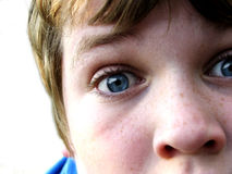 In Your Face. Close up of a teen boy's face with a questioning expression with a white background stock photo