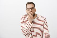 Your face make me puke. Portrait of disgusted european guy feeling unwell, covering mouth with palm and feeling dizzy. While wanting to vomit, seeing something royalty free stock photography