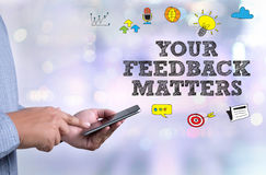 YOUR FEEDBACK MATTERS. Person holding a smartphone on blurred cityscape background royalty free stock images