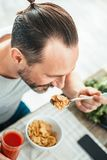 Calm unshaken man sitting and having breakfast. Your food your healthy. Calm unshaken gay man sitting by the table holding a spoon of flakes and having Stock Image