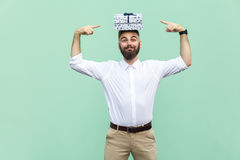 Your gift on my head. Funny young adult man holding gift box on head and pointing fingers on box. Light green background, studio shot Royalty Free Stock Images