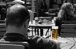 Your glass of beer. A hot day in the city, and a relaxed man sitting with his beer in an outdoor cafe Royalty Free Stock Photos