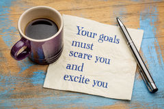 Your goals must scare and excite you. Handwriting on a napkin with a cup of espresso coffee Royalty Free Stock Images