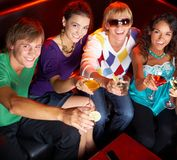 Your health!. Portrait of young people with flutes looking at you while in the nightclub royalty free stock image
