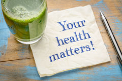 Your health matters reminder. Our health matters reminder or advice - handwriting on a napkin with a glass of fresh, green, vegetable juice stock photo