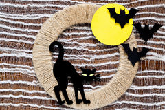 Your idea for Halloween: a black cat and bats. Halloween decoration idea: a black cat made of paper and bats on a background of yellow moon on jute ring Royalty Free Stock Image