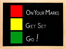 On Your Mark, Get Set, Go on blackboard. On Your Mark, Get Set, Go written on blackboard or chalkboard with traffic light red yellow green colors Stock Image