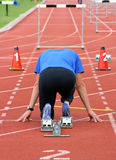 On your marks. Athlete ready to start the hurdles royalty free stock photos