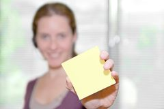 Your Message on a Sticky Note. Young woman shows your sticky note in a bright office. Sharp focus on note royalty free stock photo