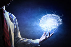 Your mind abilities . Mixed media. Businessman holding digital image of brain in palm Royalty Free Stock Image