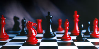 Your move. Red and black chess pieces shot on black and white chess board-hi res scan from film Stock Photography