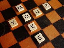 Your Move. What is your next move? Scrabble letters on wooden chessboard Royalty Free Stock Image