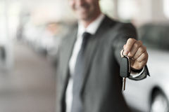Your new car keys. Smiling car salesman handing over your new car keys, dealership and sales concept royalty free stock images