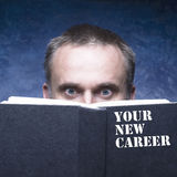 Your new career written on black book. Mature man behind book on Royalty Free Stock Photography