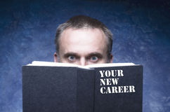 Free YOUR NEW CAREER Written On The Cover Of The Book, Mature Man Being Focused And Hooked By Book,surprised Young Man Reading Open Boo Royalty Free Stock Photos - 59012538