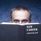 Your new chapter written on black book. Mature man behind book o stock image
