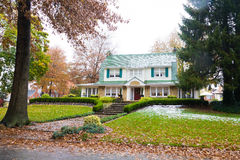 Your New Home. Fall colors surround the house and the footpath that leads you through its highly manicured lawn to the front door. Snow sits on the roof giving Stock Images