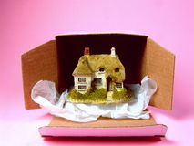 Your New Home. A miniature replica of a romantic-looking house, partly removed from a cardboard box. A symbolic representation of buying a new home Royalty Free Stock Photography
