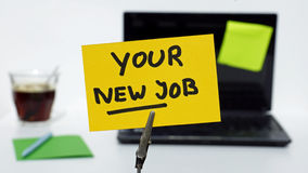 Your new yob. Your new job written on a memo at the office royalty free stock photography