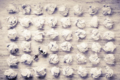 Your outstanding bright idea. Many balls of crumpled paper and light bulb among them royalty free stock photos