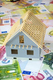 Your own four walls. Model of a house new building on a background made of Euro banknotes and coins Royalty Free Stock Images