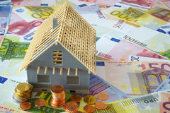 Your own four walls. Model of a house new building on a background made of Euro banknotes and coins Royalty Free Stock Photography