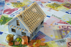 Your own four walls. Model of a house new building on a background made of Euro banknotes and coins Stock Image