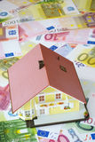 Your own home to finance. Model of a Home Ownership on a background made of Euro banknotes Royalty Free Stock Photo