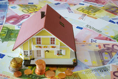Your own home to finance. Model of a Home Ownership on a background made of Euro banknotes und coins Stock Photography