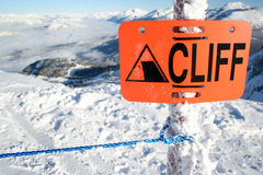 At your Own Risk. An orange sign warns of danger ahead stock photo