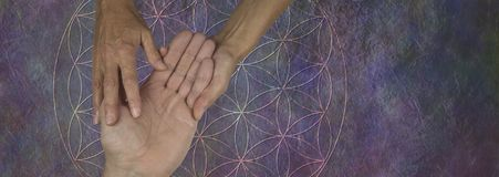 Your Palms are a map of your past and future life. Female palm reader holding a male hand examining the lines and bumps against a flower of life rustic stone Royalty Free Stock Photo