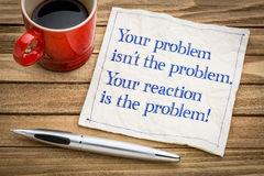 Your problem and reaction. Your problem is not the problem. Your reaction is the problem. Inspirational handwriting on a napkin with a cup of coffee Royalty Free Stock Photo