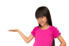 Your product here. Little asian girl standing with her hand up against white background place your product here Stock Image