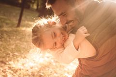Your smile is my treasure. Smiling happy father playing with daughter in park and hugging her. Close up stock photo