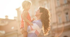 Your smile is the sun of my life. Mother playing with her daughter on city street. Copy space. Close up stock photos