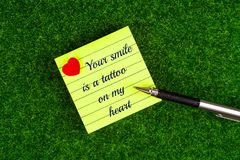 Your smile is a tattoo on my heart. In memo with heart shape and pen on grass background royalty free stock photo