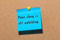 Your Story Is Still Unfolding motivation inscription written on blue sticker pinned at cork notice background Royalty Free Stock Image
