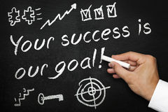 Your success is our goal. Blackboard or chalkboard with hand and chalk. Written and various symbols of success. Motivational achievement concept Royalty Free Stock Images