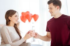 Mindful guy bringing cup of tea for girlfriend Royalty Free Stock Images
