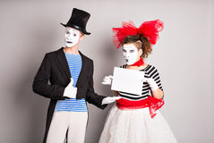Your text here. Actors mimes holding empty blank board. Colorful studio portrait with gray background. April fools day Royalty Free Stock Photos