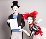 Your text here. Actors mimes holding empty blank board. Colorful studio portrait with gray background. April fools day Stock Image